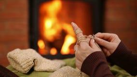 妇女递编织的羊毛袜子,休息由火-极端特写镜头 影视素材