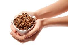 妇女递藏品在查出的杯子的咖啡豆 免版税库存图片
