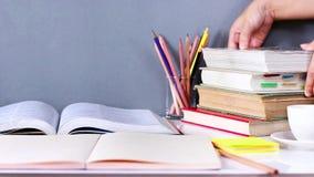 妇女递被安置的在木桌上堆积的精装书书和课本 股票录像