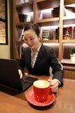 妇女递输入在咖啡shopshop的一台膝上型计算机 免版税图库摄影