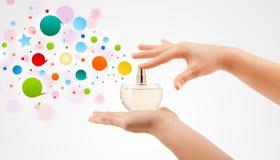 妇女递从美丽的香水瓶的喷洒的五颜六色的泡影 免版税库存图片