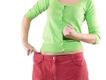 妇女通过佩带显示她的减重老大长裤 免版税库存图片
