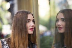 妇女通过商店窗口的时髦年轻行家,她的面孔看反射 库存照片