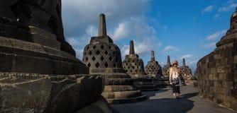 妇女通过婆罗浮屠废墟走 免版税图库摄影