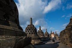 妇女通过婆罗浮屠废墟走 免版税库存图片