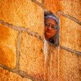 妇女通过小窗口看  免版税图库摄影