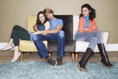 妇女通过拥抱在沙发的夫妇 免版税库存照片