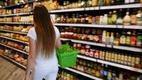 妇女通过有绿色plastik手提篮的超级市场走,在架子之间,选择物品 影视素材