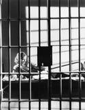 妇女通过牢房酒吧  免版税图库摄影