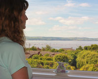 妇女通过窗口敬佩海景 库存图片
