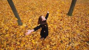 妇女通过金黄黄色叶子和愉快微笑 影视素材