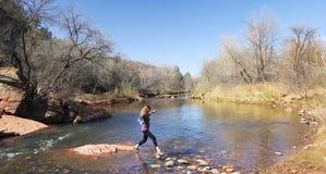 妇女通过飞跃横渡小河 库存图片