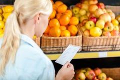 妇女通过购物单看在堆果子附近 图库摄影