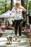 妇女遛在似犬时装表演的狗 免版税库存图片