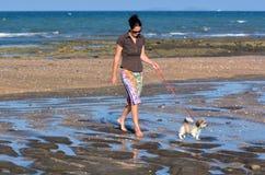 妇女遛她的小狗 免版税库存图片