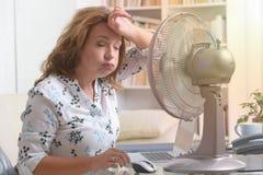 妇女遭受在家热在办公室或 免版税库存照片
