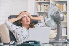妇女遭受在家热在办公室或 免版税库存图片