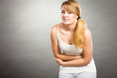 妇女遭受腹部痛苦 免版税库存照片