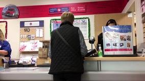 妇女邮寄的信件的行动在邮局的在顾客里面使小店服麻醉剂 股票视频