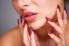妇女部份画象有红色修指甲和至善至美的脸色的 免版税图库摄影