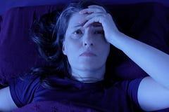 妇女醒的床夜失眠 免版税库存照片