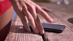 妇女采取手机,智能手机的` s手近景说谎在桌,在女用贴身内衣裤的性感的妇女` s臀部上在背景 股票录像