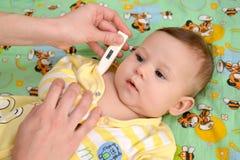 妇女采取温度给病的婴孩电子温度计 免版税库存照片