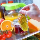 妇女采取葡萄从开放冰箱的 免版税图库摄影