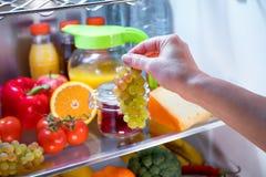 妇女采取葡萄从开放冰箱的 库存图片