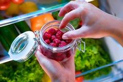 妇女采取从开放冰箱的新鲜的莓 库存照片