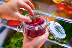 妇女采取从开放冰箱的新鲜的莓 库存图片