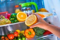妇女采取从开放冰箱的桔子 免版税图库摄影