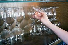妇女采取从架子的一块玻璃 库存图片