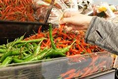 妇女采摘在大型商场里面的` s手的行动绿色和炽热胡椒 免版税图库摄影
