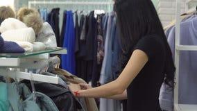 妇女采摘衣裳在商店 更新衣橱 股票录像