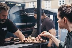 妇女采样烤了肉在Spitalfields市场,伦敦,英国里面的一个Smokoloco摊位 库存图片