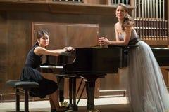 妇女钢琴演奏家坐在钢琴和美丽的歌手 图库摄影