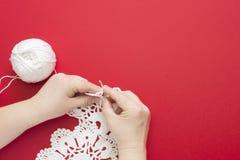 妇女钩编编织物的白色鞋带小垫布 棉纱品、钩针编织毛线球顶视图和钩针 图库摄影