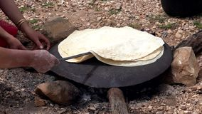 妇女铺开tranditional伊朗人Qashqai平的面包3 -转动在平底锅的面包在火 影视素材