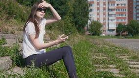 妇女键入在坐在公园的电话的一则消息 股票录像