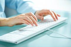 妇女键入在键盘的办公室工作者 免版税图库摄影