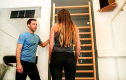 妇女锻炼在她的健身房的健身辅导员帮助下  库存图片