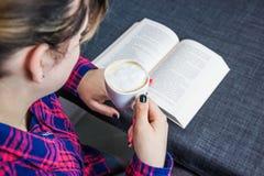 妇女阅读书和咖啡 免版税库存照片
