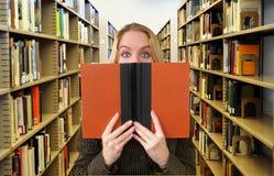 妇女阅读书在图书馆里 库存照片
