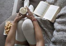 妇女阅读书特写镜头在家在有热的chocolatemilk和曲奇饼的长沙发 库存图片