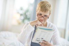 妇女阅读书在卧室 免版税库存图片
