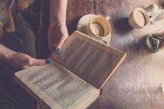 妇女阅读书在早上和饮用的咖啡 免版税库存图片