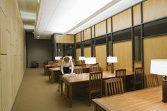 妇女阅读书在空的图书馆里 库存照片