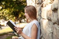 妇女阅读书对老石墙 免版税库存照片