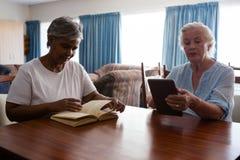 妇女阅读书,当使用片剂的朋友在桌时 免版税库存照片